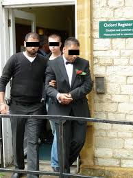 Suspect in handcuffs being taken away for internet scams and frauds