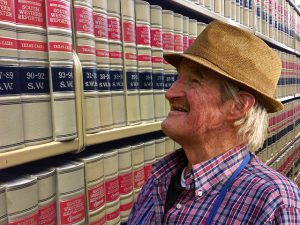 Man Looking At Shelf Of Law Books For Legal Help For Scams