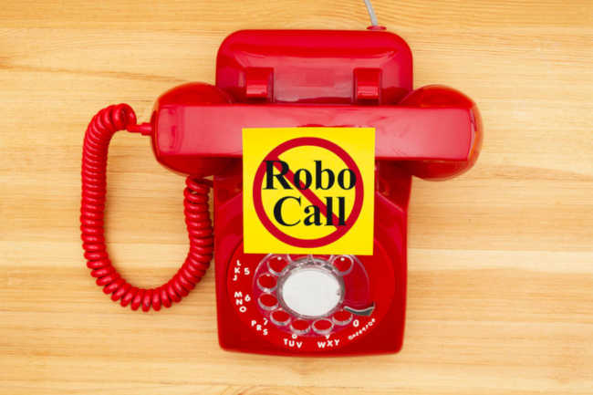 No Robo Call message on a sticky note on a red old retro rotary landline phone on a wood desk For Covid Scams You Can Avoid