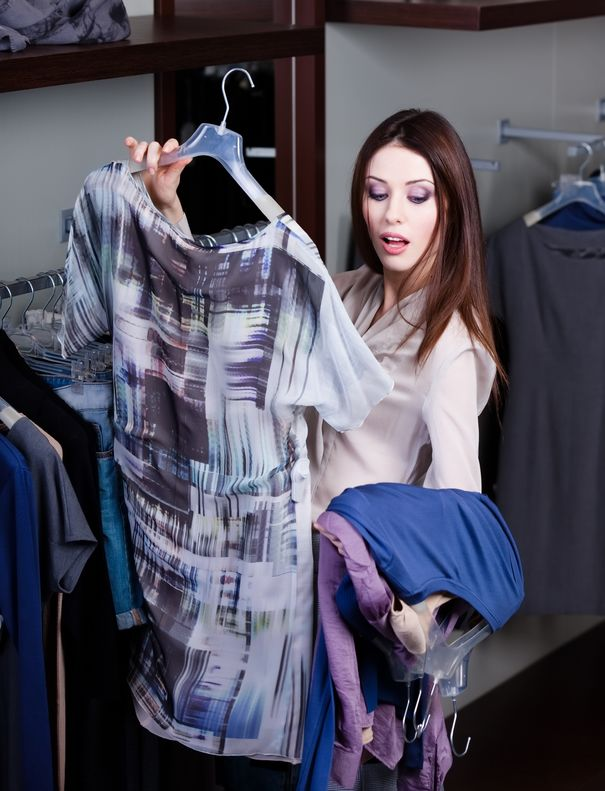 Woman Holding Dress Deciding to Buy While Shopping For Mystery Shopper Scams List