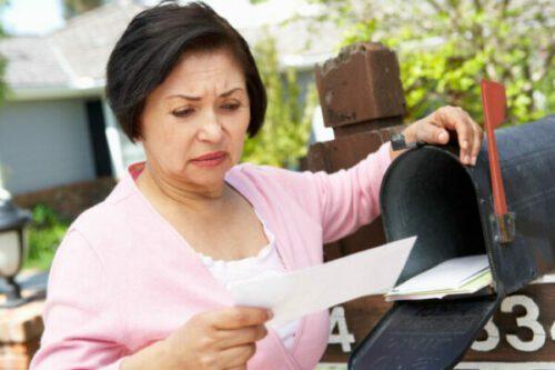 Worried Senior Hispanic Woman Checking Mailbox For Mystery Shopper Scams List